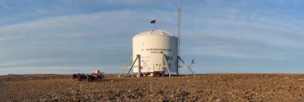 Une construction circulaire sur pilotis avec deux VTT dans un paysage aride.