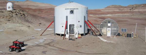Plusieurs petites constructions et des VTT dans un paysage désertique et escarpé.