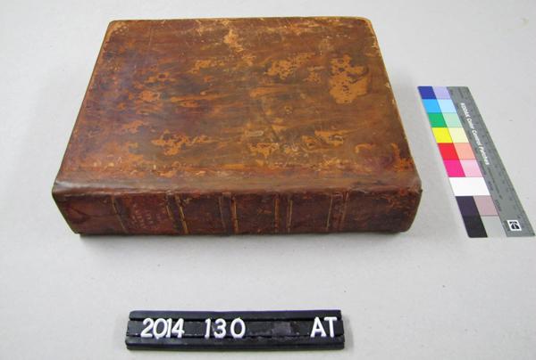 Un livre posé sur une table et dont la reliure est réparée.