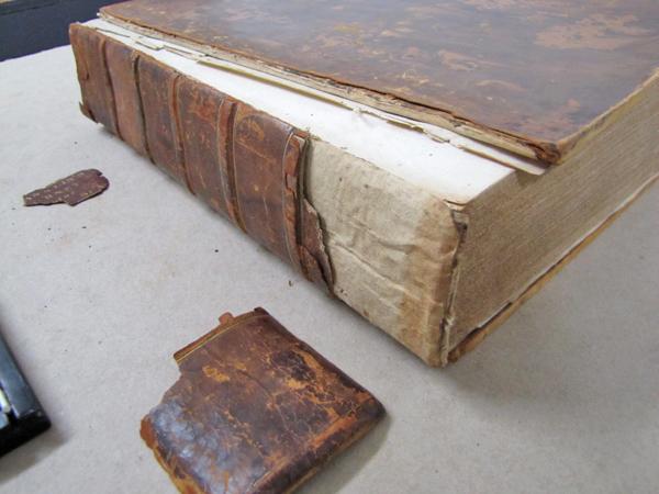 Un livre abîmé est posé sur une table, à côté de morceaux de reliure en cuir.