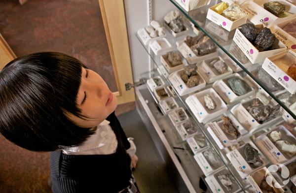 Une fillette regarde un étalage de minéraux.