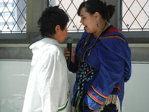 Deux visiteurs du Musée en face l'un de l'autre; l'un tient un microphone.