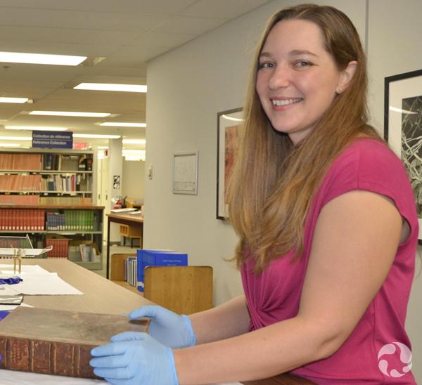 Une femme debout près d'une table où est posé un livre ancien.