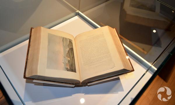 Un livre ouvert sur une page illustrée dans une vitrine d'exposition.