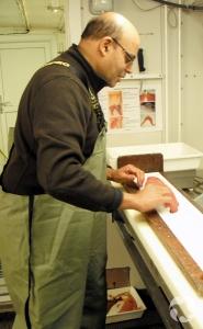 Un homme portant des pantalons de pêche mesure un poisson, debout devant une table de travail.