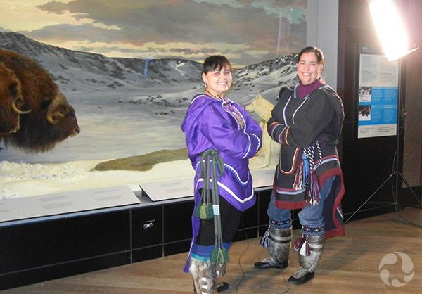 Deux femmes en costume traditionnel inuit debout devant un diorama.