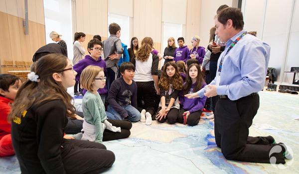 Ed Hendrycks parle avec des élèves qui explorent la carte.