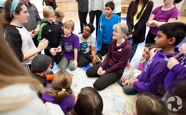 Jennifer Doubt entourée d'élèves captivés par l'exploration de la carte de sol.