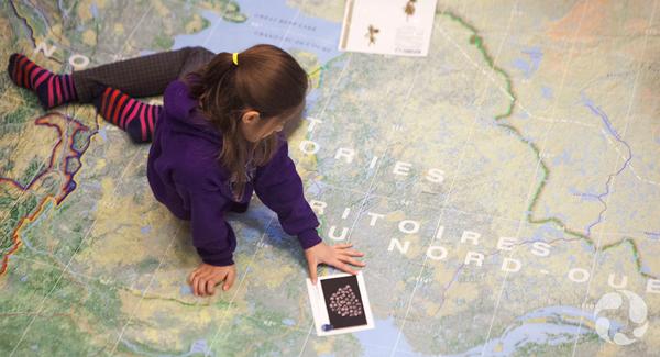 Un élève tient une fiche de spécimen en explorant la carte.