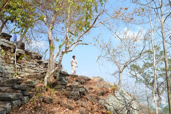 Une personne debout sur un escalier de pierre grossier, au sommet d'une colline.