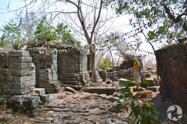 Une personne debout près de murs formés de blocs de pierre.