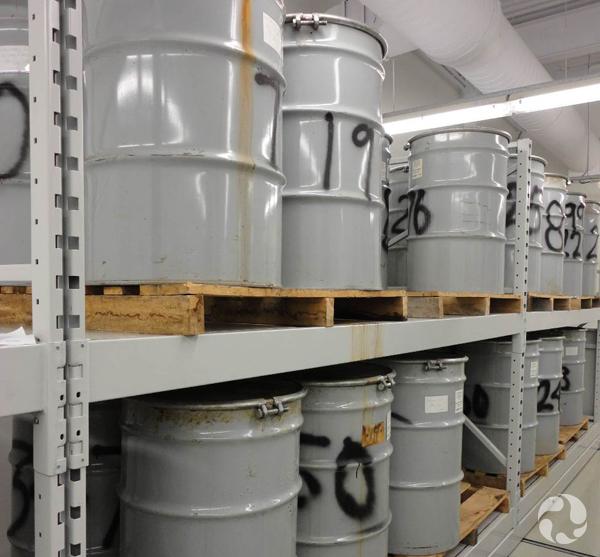 Gros barils de métal sur des étagères.