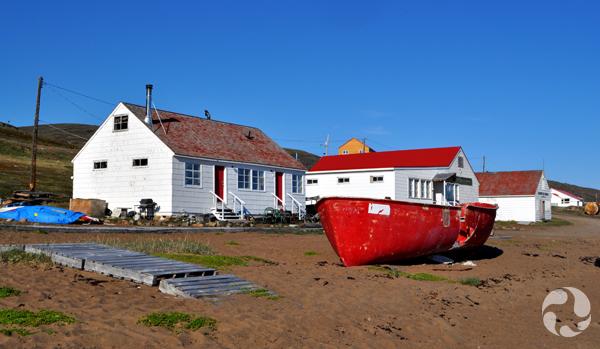 Un bateau tiré au sec sur le sable devant de petits bâtiments.