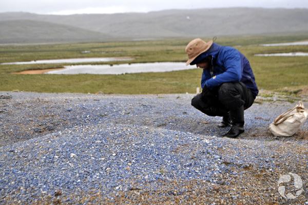 Un homme accroupi examine le sol.