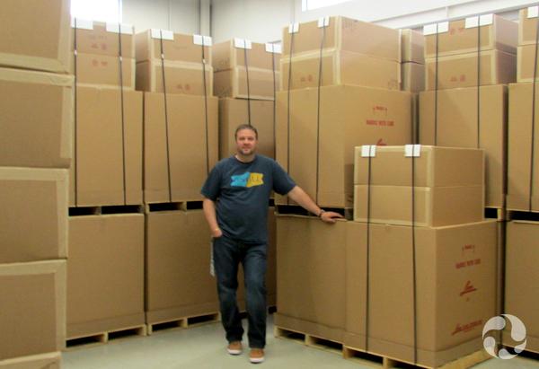 Un homme debout dans un entrepôt entouré de hautes piles de boîtes.