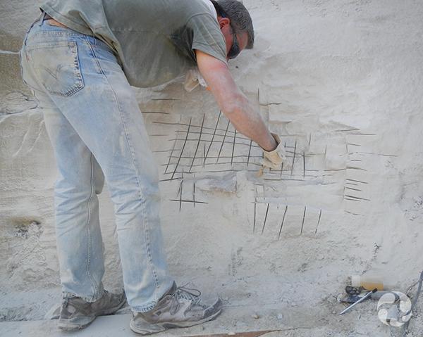 Le technicien Alan McDonald se penche pour quadriller le mur de roche.
