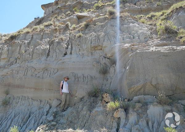 Jordan Mallon debout près d'une falaise contenant le fossile incrusté.