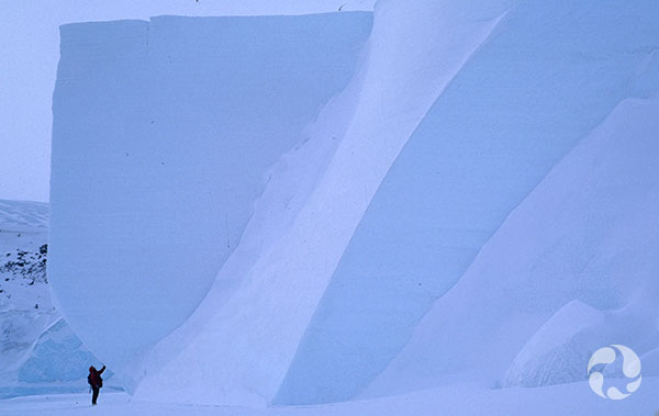 Une personne au bas d'un immense iceberg.