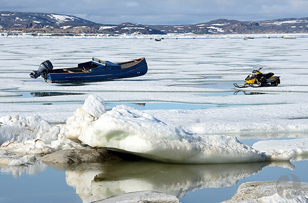 A motorboat and snowmobile sit on the ice.