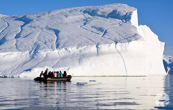 Plusieurs personnes dans un canot pneumatique devant un iceberg.