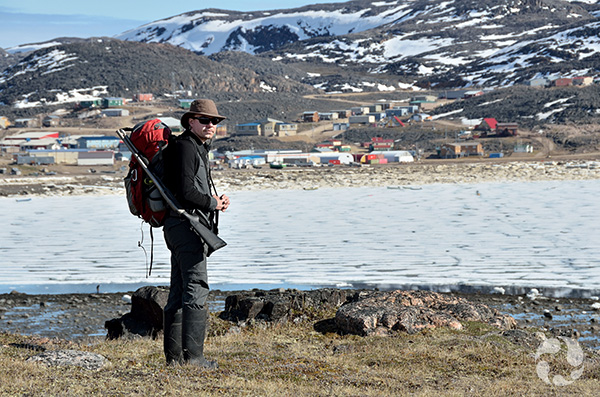 A man carrying a rifle stands with a bay and Cape Dorset in the background.