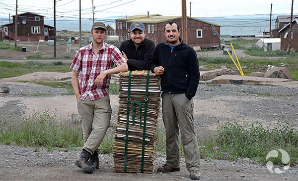 Trois hommes appuyés sur une presse de plantes.