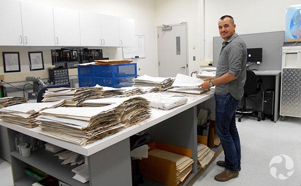 Un homme devant des piles de feuilles de spécimens dans un laboratoire.