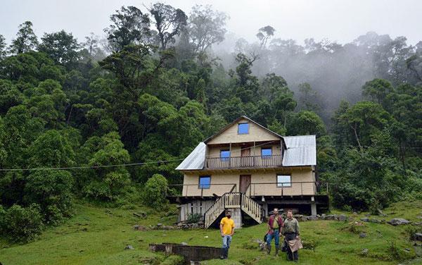 Trois hommes devant une maison au flanc d'une montagne.