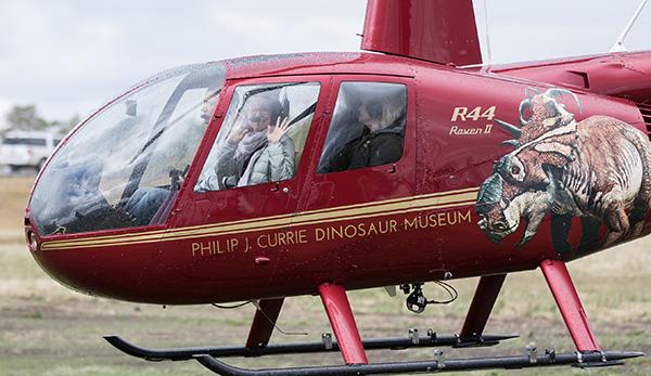 Une femme assise dans un hélicoptère agite la main.
