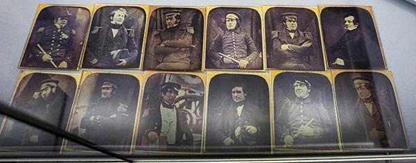 Une douzaine de photographies anciennes dans une vitrine.