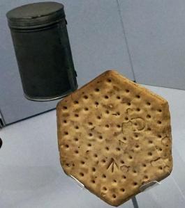 Un biscuit et une boîte métallique dans une vitrine.
