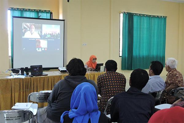 Des adultes assis regardent un écran à l'avant d'une classe.