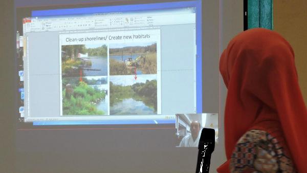 Une femme est debout, un micro à la main, devant un écran montrant plusieurs images.