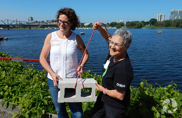 Deux femmes près de la rivière tenant un bloc de ciment.