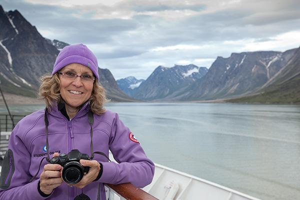 Meg Beckel sur la proue d'un navire dans l'Arctique.