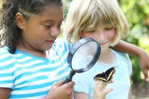 Deux filles observent un papillon de près.