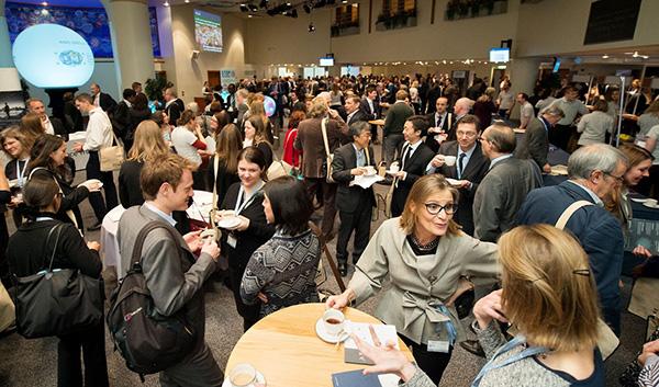 Une foule de délégués à la conférence debout en train de discuter dans un grand hall.