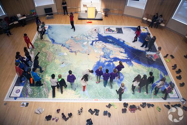 Des enfants traversent une carte géante de l'Arctique.