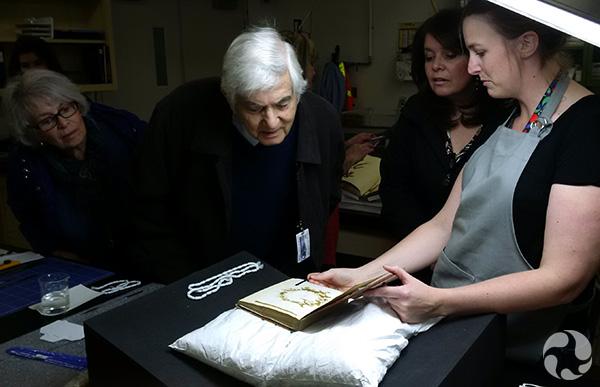 Des personnes examinent un livre ouvert sur une table.
