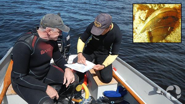Deux hommes regardent une carte dans une petite embarcation.