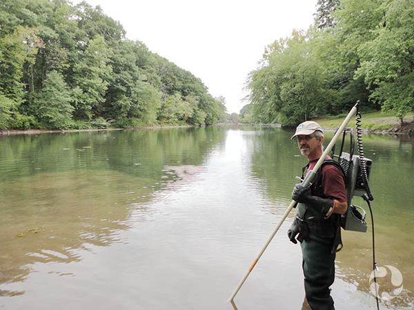 Un homme dans un ruisseau tenant un équipement de pêche électrique.