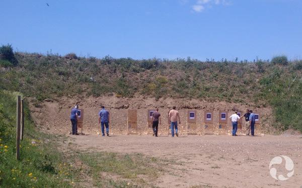 Des hommes examinent les cibles devant eux.