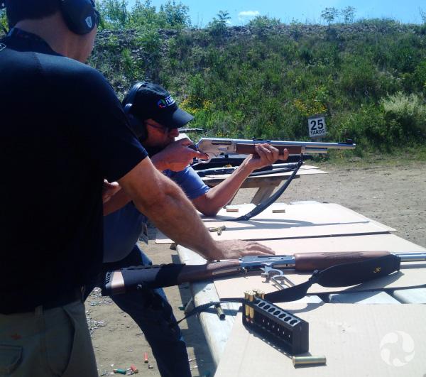 Un homme tire à la carabine en prenant appui sur une table.