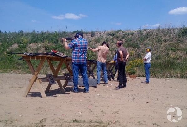Quatre hommes en rangée tirent à la carabine.