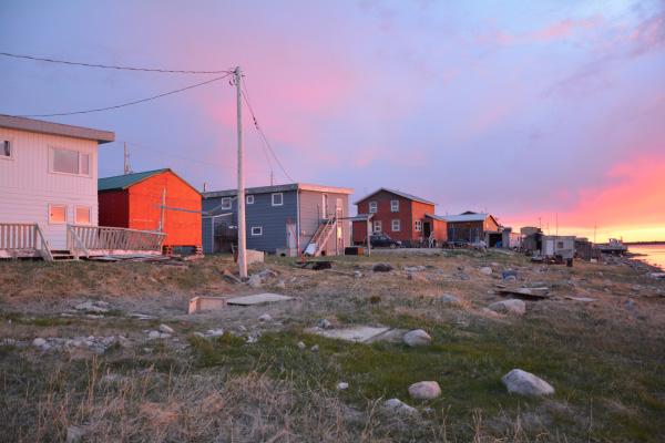 Maisons d'Arviat au premier plan et coucher du soleil en arrière plan.