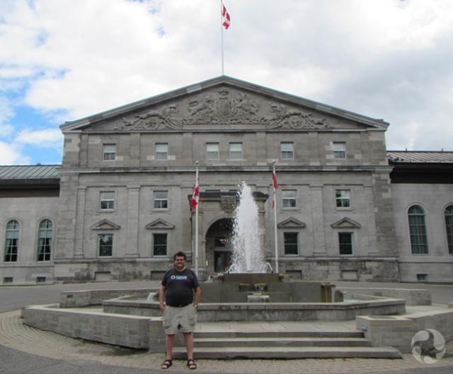 Un homme posant devant une fontaine et un édifice.