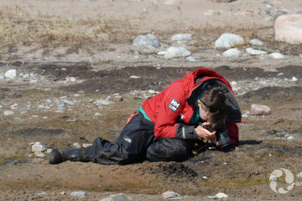 Une femme assise au sol.