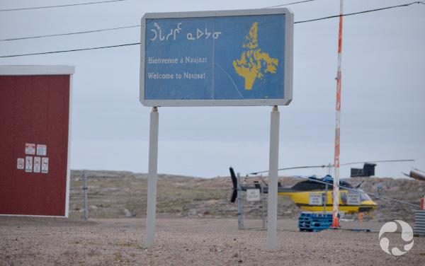 Un panneau souhaitant la bienvenue à Naujaat en inuktitut, en français et en anglais, avec un hélicoptère et un édifice en arrière-plan.