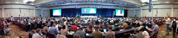 Personnes assises dans une salle de conférence.