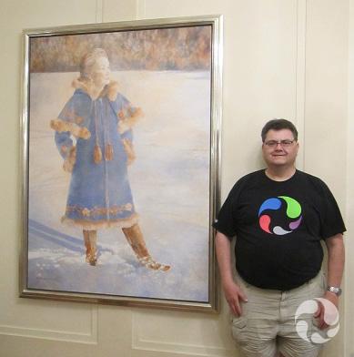 Un homme pose près d'une peinture exposée sur un mur.